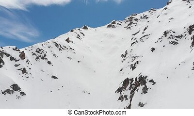 aerial view. A group of skiers and snowboarders, high in the mountains, prepare for a steep descent along the snowy couloir. Off-piste professional skiing. North Caucasus