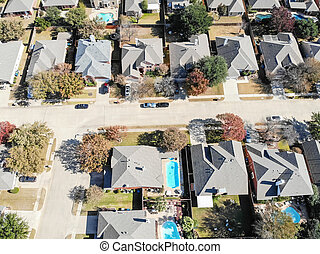 Aerial view a rich subdivision neighborhood with swimming pool and bright autumn leaves
