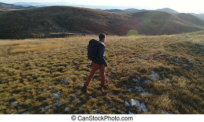 tourist with a backpack walks among the hills - aerial view...