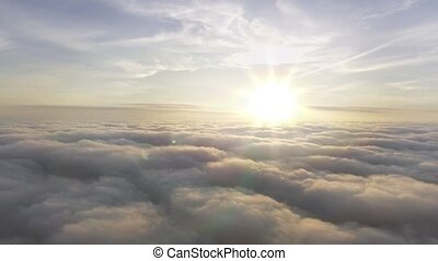 aerial view above the clouds towards the sun