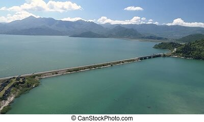 Aerial view at the dam with railroad and vehicular bridge leading through the Skadar lake. Route from Podgorica to Adriatic coast. Montenegro