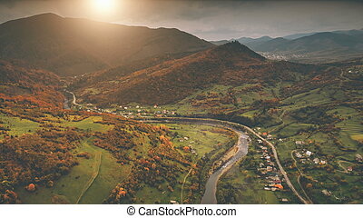 Aerial View: autumn canyon village along the river