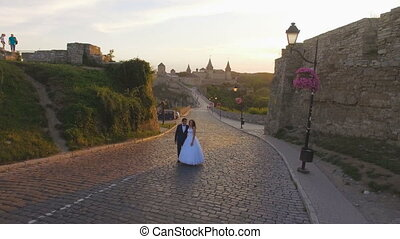 Aerial view: beautiful couple walking at the antique big castle 4k