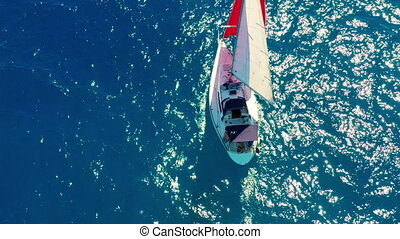 Aerial view. Beautiful sailing yacht with a red sail is sailing on the emerald sea on a sunny day.