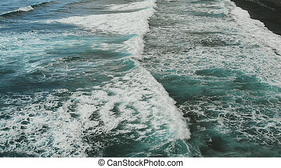 Aerial view. Beautiful waves of turquoise color fall on the coast with black sand. Tenerife, Playa del Socorro