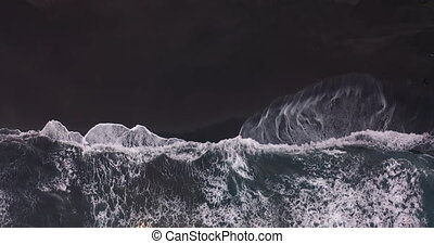 Aerial view. Black volcanic sand beach. Waves roll in one after another