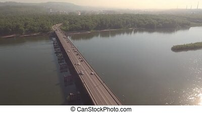 Aerial view. Bridge with traffic over the river w on a sunny day in small city. 4K
