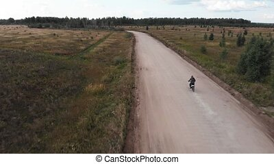 Aerial view, Camera follows of the motocross rider riding on his motorcycle on the off-road track
