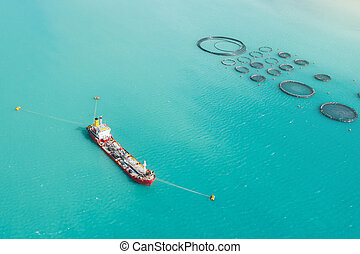 Aerial view cargo tanker moored in the bay, near the farm for growing fish.