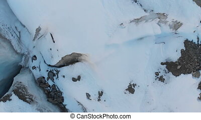 Aerial view close-up edge of a flowing glacier covered with...
