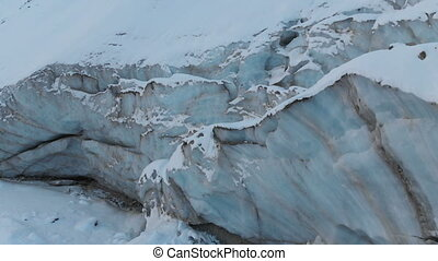 Aerial view close-up edge of a flowing glacier covered with snow and stones high in the mountains. Natural destruction of melting glaciers and global warming