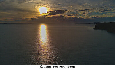 Aerial view Cloudy sunset with the reflection of the sun on the quiet sea.