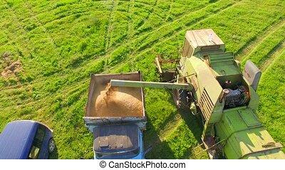 AERIAL VIEW. Combine Harvester Unloading Wheat Grain Into...