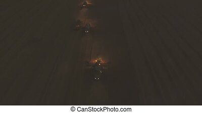 Aerial view. Combine Night Harvester Gathers the Wheat crop 4k video