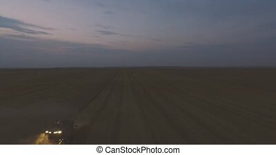 Aerial view Combine Night Harvester Gathers the Wheat crop
