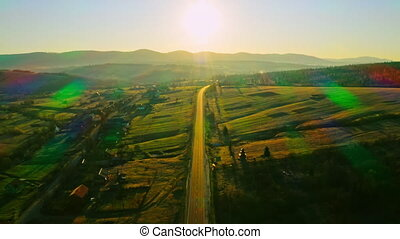 drone flies above road road in soft sunrise sunlight sky with sun rays mountains landscape