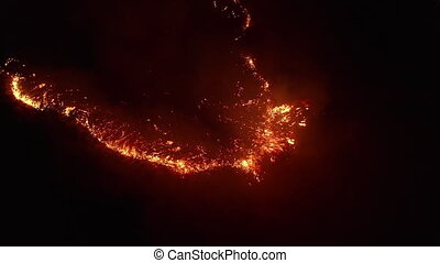 Aerial view. Dangerous fire in the field. Night fire, natural disaster