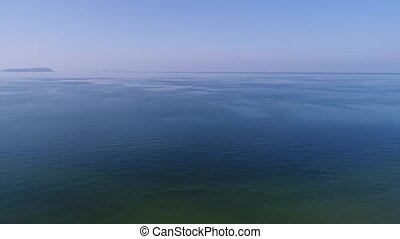 aerial view, descent in of calm, blue sea - aerial drone...