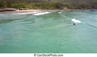 distant surfer beginner steps up on surfboard on ocean wave...