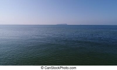 aerial view, dolly in of calm, blue sea - aerial drone...