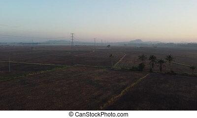 Aerial view dry empty field near electric pylon