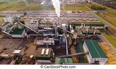 Aerial view. Eco-friendly woodworking factory. Smoke comes out of chimney, tube. Emission to atmosphere from industrial pipe. Camera flies into smoke. People destroys planet. Wood processing plant