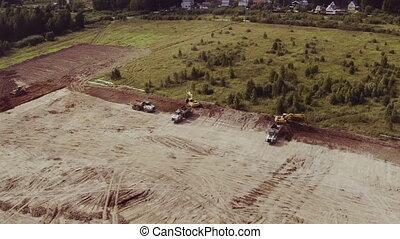 Aerial view excavators scoop load a dump trucks - aerial...