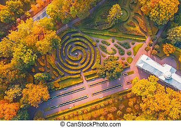 Aerial view flight over autumn valley park with trees, walking paths among the bushes of mazes.