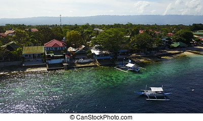 Aerial view flying over amazing of sandy beach with tourists swimming in beautiful clear sea water of the Sumilon island beach landing near Oslob, Cebu, Philippines.