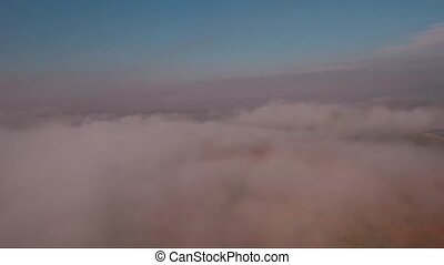 Aerial view, flying through and over the fog at sunset, countryside with a road