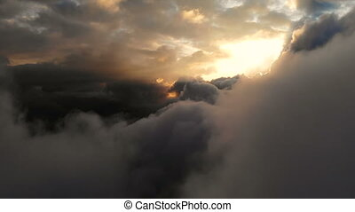 Aerial view flying through cumulus thunderclouds at sunset. Gold colored sunset cloudiness in high contrast. Real sky. The concept of dreams and weather forecast. Low key
