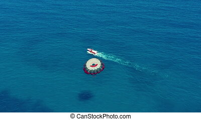 Aerial view. Flying with Parachute Behind a Boat. Extreme Water Sport in the Sea. Parasailing.