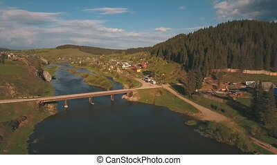 aerial view from a height on the river and village near a forest