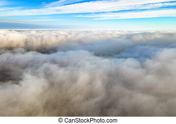 Aerial view from above of white puffy clouds in bright sunny day.