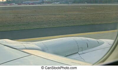 aerial view from airplane window on aircraft steel jet engine moves by empty runway