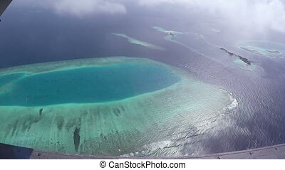 Aerial View From Airplane Window On Maldivian Islands. With...