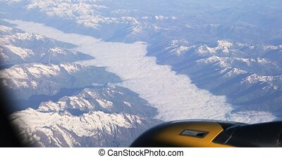Aerial View From Airplane Window On Snowy Top Of Tatra Mountains In Summer Day. High Attitude.