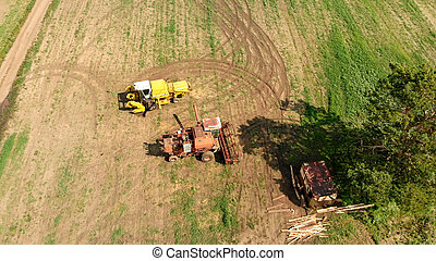 Aerial view from drone of agriculture combine and harvesters on wide brown field