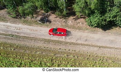 Aerial view from drone on a red car driving along the empty...