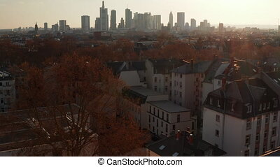 Aerial view from drone. Tilt up reveals skyscraper skyline of downtown against sun. Frankfurt am Main, Germany. 4K.