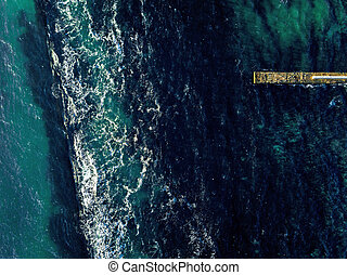 Aerial view from drone to a seascape of turquoise color water and stone mole in a sea clear water with foam waves. Top view. Copy space.