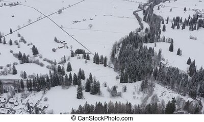 Aerial view from height on the road through a snow-covered field and trees, cloudy weather