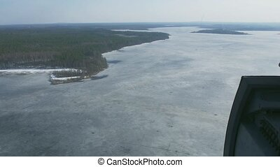 Aerial view from helicopter fly above frozen lake at green forest. Camera inside. Height. Ice