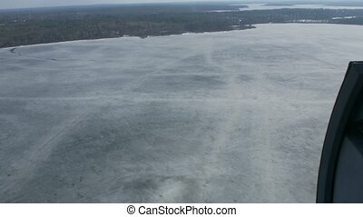 Aerial view from helicopter fly above frozen lake at green forest. Camera inside. Ice water surface