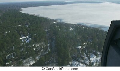 Aerial view from helicopter fly above green forest and frozen lake. Camera inside. Landscape. Ice