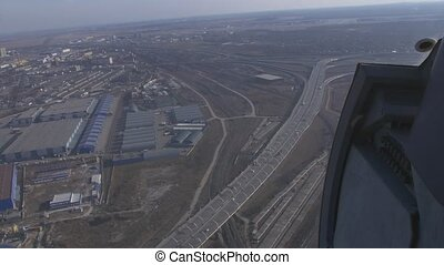 Aerial view from helicopter fly above city. Height. Motorway with cars, road junction. Sunny day.