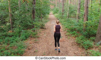 Aerial view from the Back to the Young Woman who Runs along the Path in a Pine Thick Forest