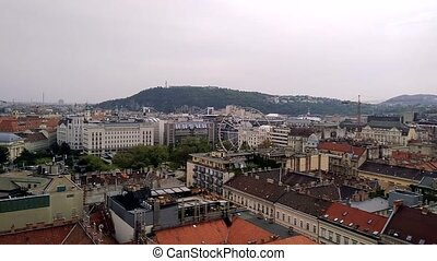 Aerial view from the Saint Istvan basilica to Ferris wheel in Budapest. Roofs of houses in the historical part of Budapest