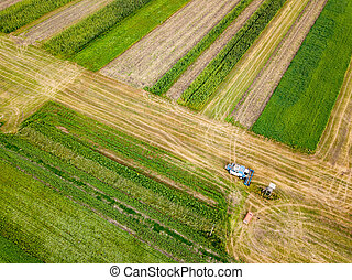 Aerial view frome a drone of combine plowing the ground after harvesting on the field in the autumn time.