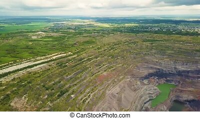 Aerial view industrial of opencast mining quarry with lots of machinery at work - view from above. Extraction of gold, copper.